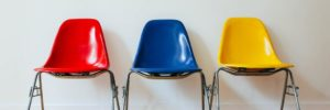 Signifying job candidate comparison, three molded plastic chairs with metal legs sit in a row against a white wall on a hardwood floor. The chair on the left is red, the chair in the middle is blue, and the chair on the right is yellow.