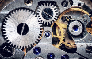 A close-up of a clock mechanism's steel and metal gears signifies the many features that determine how personality tests work.