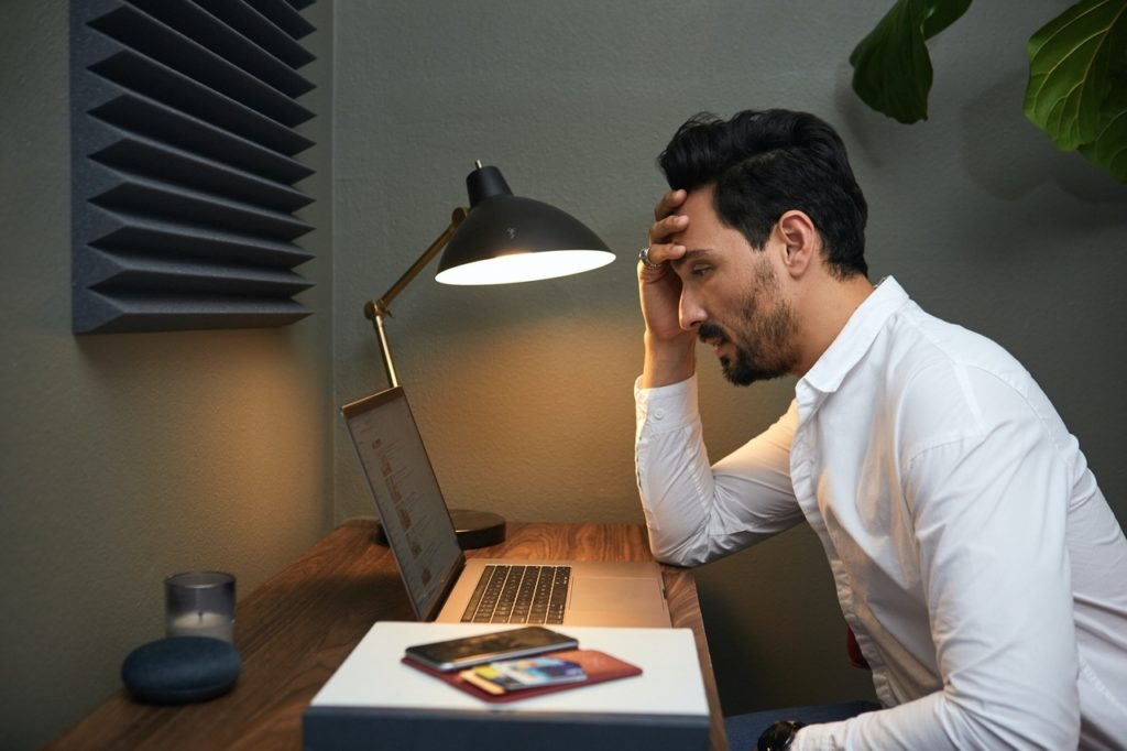 A dark-haired, bearded businessman wearing a white button-up shirt sits in front of a laptop computer illuminated by a black metal desk lamp. Experiencing interview fatigue, he rests his forehead in his hand. Also on his desk are a candle, a smartphone, and some books. Behind him is a houseplant. Accordian-shaped wall décor is mounted above his desk.